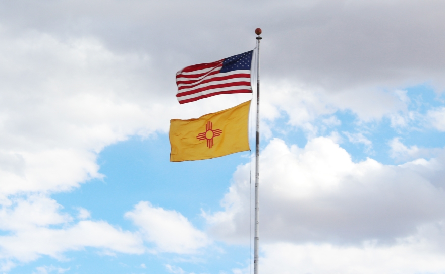 The New Mexico state flag flies under the national flag of the United States